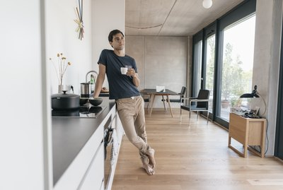 Young man holding cup of coffee in kitchen at home