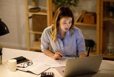Young woman doing finances at home using laptop