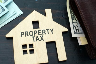 Property tax sign on a house model.