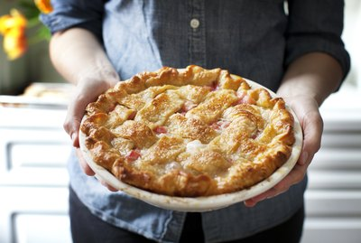 Midsection of woman holding baked rhubarb pie while standing at home