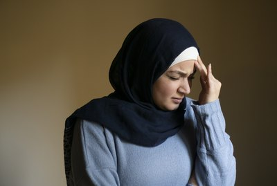 Stressed Muslim woman hand on head