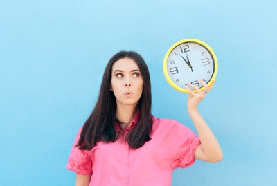 Cheerful Woman Holding a Clock on a Blue Background