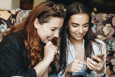 Beautiful plus size women with red hair looking at a smartphone screen smiling holded by her girlfriend while sitting in coffee shop.
