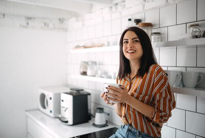 Young woman sitting on kitchen counter and enjoying morning coffee