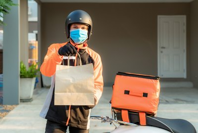 Delivery Asian man wear protective mask in orange uniform and ready to send delivering Food bag in front of customer house with case box on scooter, express food delivery and shopping online concept.