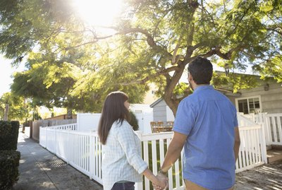 Latinx couple holding hands beneath sunny tree in front yard