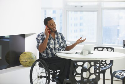 Black businessman in wheelchair talking on cell phone at table