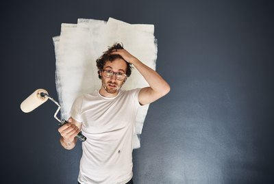 Portrait of a man looking into camera with a paint roller in one hand, frustrated and overwhelmed