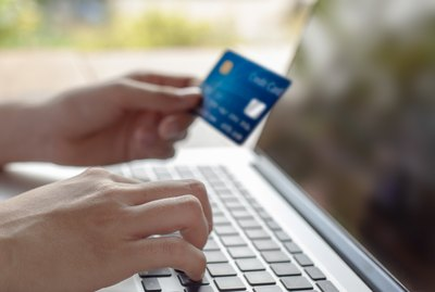 Woman hand holding blue credit card and using a modern laptop, typing and texting