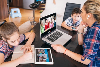 Mother talk with friends on laptop while watching two kids staying home Homeschooling and distance learning
