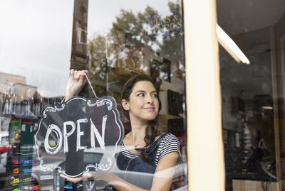 Confident female small business owner hanging Open sign in shop window