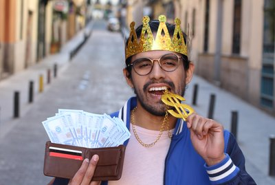 Crowned young guy with full wallet