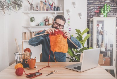 Bearded man knitting at home using laptop for watching online tutorial