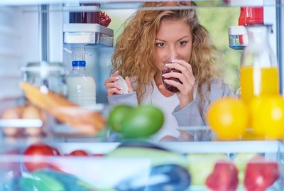 Woman smelling jam in front of fridge full of groceries.