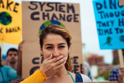 """People with signs demanding """"climate change"""" Justice and Climate. Group of demonstrators fight for climate change. Symbol of woman silenced by politics – Image"""