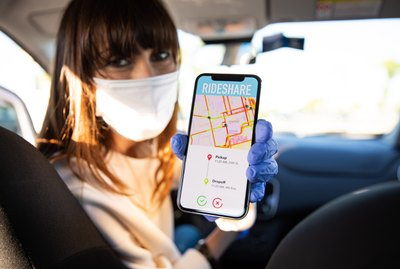 Car sharing driver showing destination to passengers on smart phone