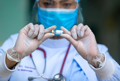 Female doctor wearing protective mask to Protect Against Covid-19 looking medicine vial vaccine bottle on hand holding.