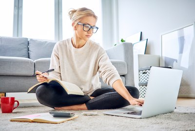 Woman using laptop paying bills online and managing home budget