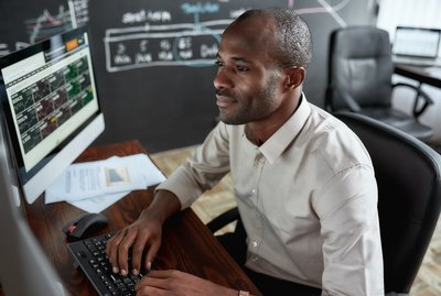 Earn more and count more. Cheerful african male trader sitting by desk and studying analytical reports using pc in the office.