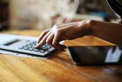 Close up of businesswoman hands using calculator.