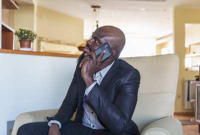 African Man Having Good News on Mobile at Home Office