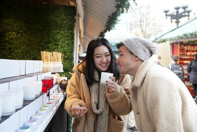 Two Millennials, one Caucasian male and one Asian female, shop for candles at outdoor holiday market in the city.