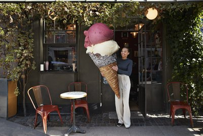 Smiling woman carrying large ice cream cone at sidewalk cafe