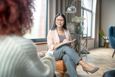 Pleasant psychologist wearing grey trousers smiling to client