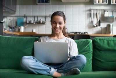 Happy smiling woman sitting on sofa and using laptop
