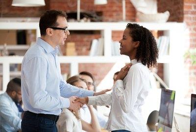 Executive team leader handshaking excited proud african employee, rewarding concept
