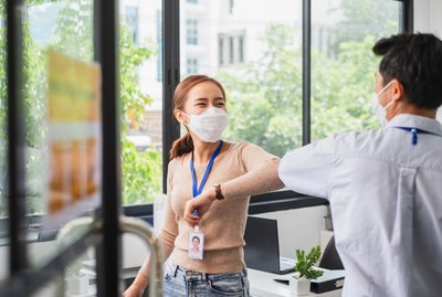 Asian businessman greeting with elbow bump or shaking elbow in working office to avoid touching due to infection of coronavirus covid-19, new normal life and social distancing concept