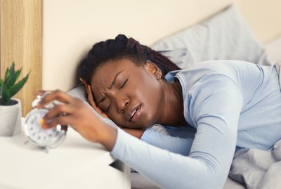 Woman Turning Off Alarm-Clock Touching Head Waking Up In Bed