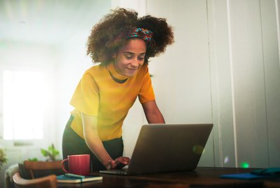 Woman stood using laptop at home