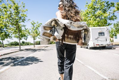 Carefree young woman carrying skateboard in the street, rear view