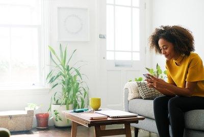 Woman sat on sofa using smart phone