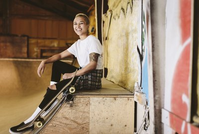 Portrait happy young female skateboarder sitting on ramp at indoor skate park