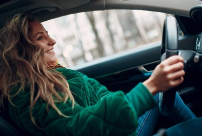 Young woman smiles and drives the car