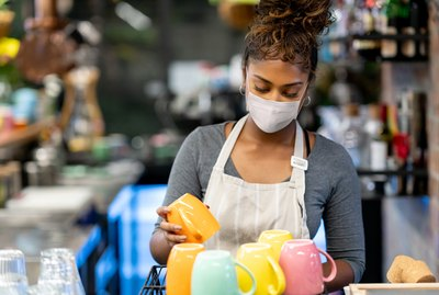 Waitress working at a cafe wearing a facemask during the COVID-19 pandemic