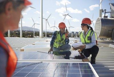Engineers examining solar panels at alternative energy power plant