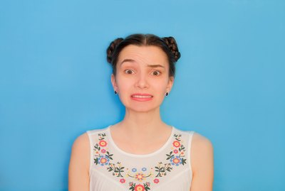 Funny cute girl on a blue studio background. Bright emotional female portrait. Failed grimace face