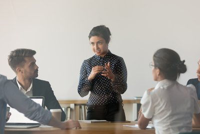 Female indian coach hold meeting brainstorming with employees