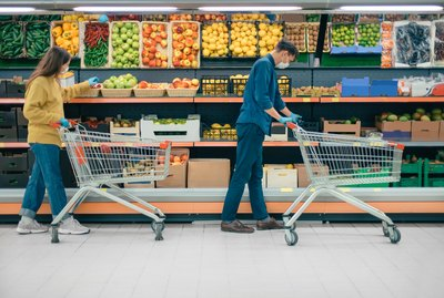 man and a woman with shopping carts in a supermarket during the quarantine period