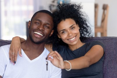 African couple sitting on couch holding keys from new house