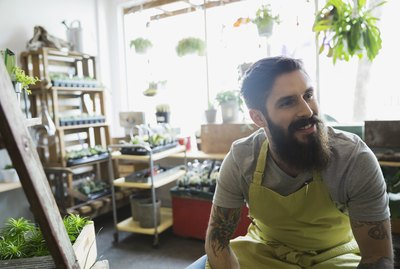 Smiling terrarium shop owner with beard looking away