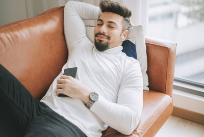 a middle eastern man lying down on sofa in living room relaxing taking a break in the afternoon