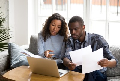 Serious African American couple discussing paper documents