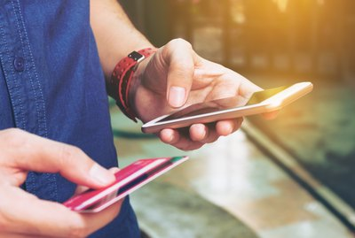 Midsection Of Man With Credit Card Using Smart Phone On Footpath