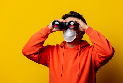 guy in face mask looking in to binoculars
