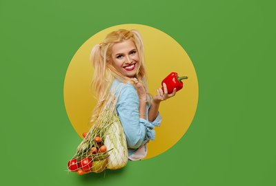 Young woman collected fresh vegetables in a string bag on a green background. Peeks out of a round hole in the wall. Retro and pin up style. The concept of proper nutrition and vegetarianism.