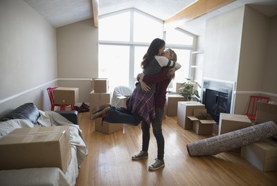 Affectionate, playful lesbian couple hugging and kissing, moving into new house